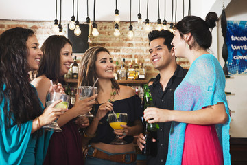 Hispanic friends having drink in bar