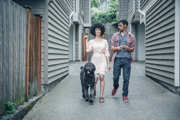 Mixed race mother and son walking dog in suburban apartment complex