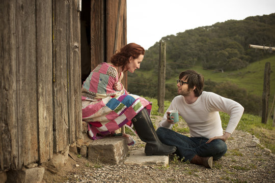Couple relaxing by barn