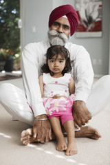 Asian girl sitting in grandfather's lap
