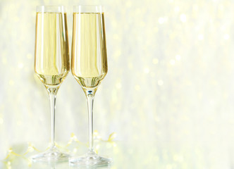 Glasses of champagne on lights background