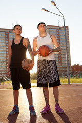 Two friends are standing on the basketball court with balls and looking toward. Shooting in full growth.