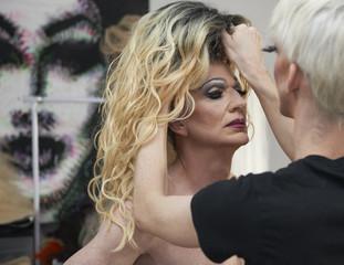 Caucasian drag queen fixing colleague's wig in bathroom