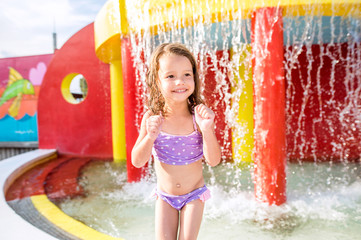 Girl under splashing fountain. Summer heat and water.