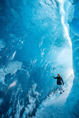 Woman walking through glacial  ice cave, Iceland