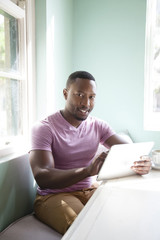 Black man using digital tablet at table