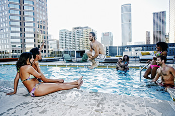 Friends watching man do cannonball dive into urban swimming pool