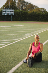 Woman stretching on football field
