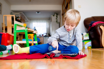Boy with broken leg in cast playing on tablet.