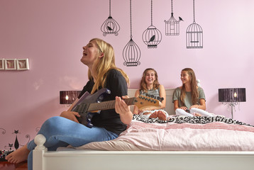 Caucasian girl playing guitar and singing on bed for friends