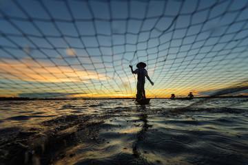 Fisherman throwing net in river during sunset