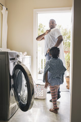 African American father and daughter doing laundry