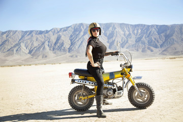 Woman standing on motorcycle in desert