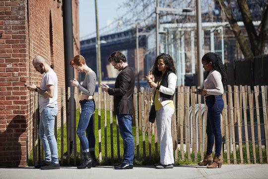 People in line on sidewalk using cell phones