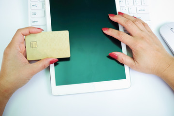 Woman's hands holding credit card and using laptop. Online shopping