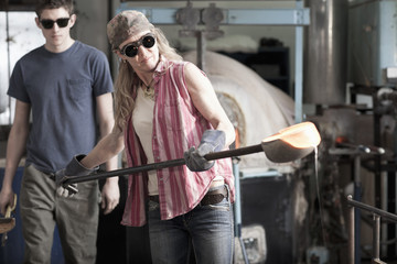 Caucasian woman in glass blowing studio