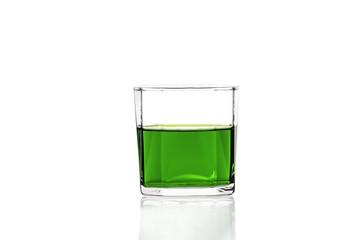 Green water in glass with reflection on white background
