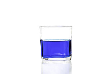 Blue water in glass with reflection on white background