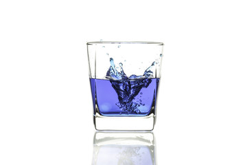Water splash in glass with reflection on white background