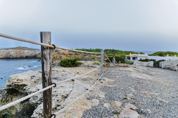 rickety fence on the rock cliff ibiza,spain,summer