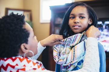 Black mother arranging scarf of daughter