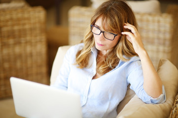 Smiling mature woman working on laptop at home