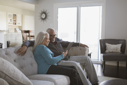 Older couple using digital tablet on sofa