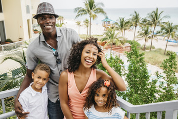 Family smiling on steps overlooking beach
