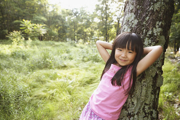 Girl leaning against tree outdoors