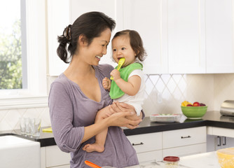 Mother holding baby girl in kitchen