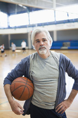 Caucasian man standing in gym with basketball