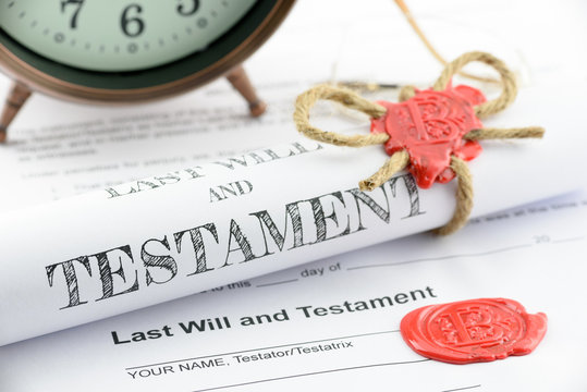 Rolled up scroll of last will and testament fastened with natural brown jute twine hemp rope, sealed with sealing wax and stamped with alphabet letter B. Decorated with an antique clock on a table.