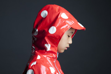 Disappointed Asian girl wearing hooded raincoat
