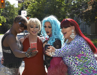 Drag queens taking cell phone pictures together on city street