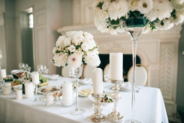 Table decor with white flowers  and candles for an event party or wedding reception