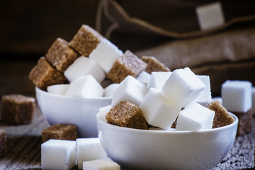 White and cane sugar in a porcelain bowls, selective focus