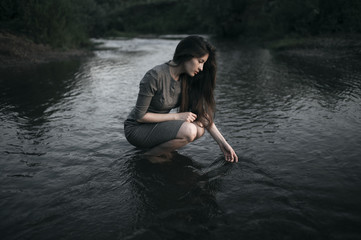 Caucasian woman crouching in remote stream