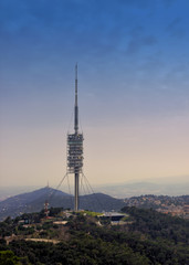 TV tower in the mountains. Torre de Collserola observation tower located on the Tibidabo hill, Barcelona, Spain