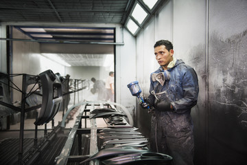 Worker spray painting in manufacturing plant