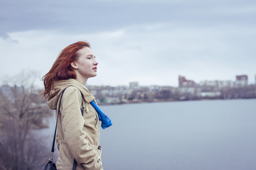 Woman with red hair standing at waterfront