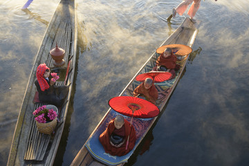 Asian gondoliers rowing canoes on river