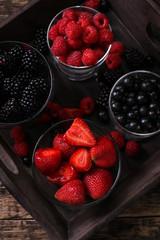 mixed strawberries, raspberries, blueberries and blackberries on vintage metal spoons