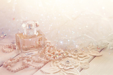 Dreamy photo of white pearls necklace and perfume bottle