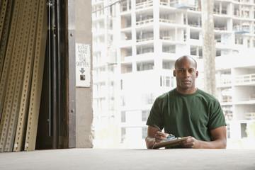 Black man standing near warehouse loading dock