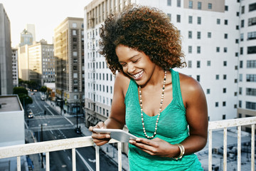 Mixed race woman using digital tablet on urban rooftop