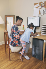 African American mother with daughter working from home