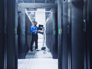 Technician using computer in server room