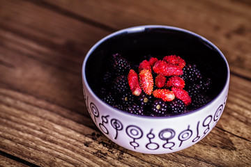 Mixed berries in plate on rustic wooden background. Close up, top view, high resolution product. Harvest Concept. Top view.