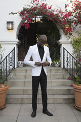 African man buttoning suit jacket