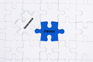 White puzzle with word INSURANCE and POLICY